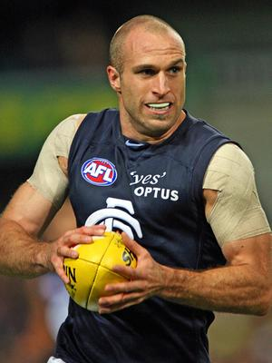 Chris Judd running with the football against West Coast